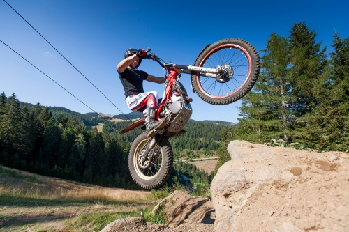 Jump over a stone with a trial bike.